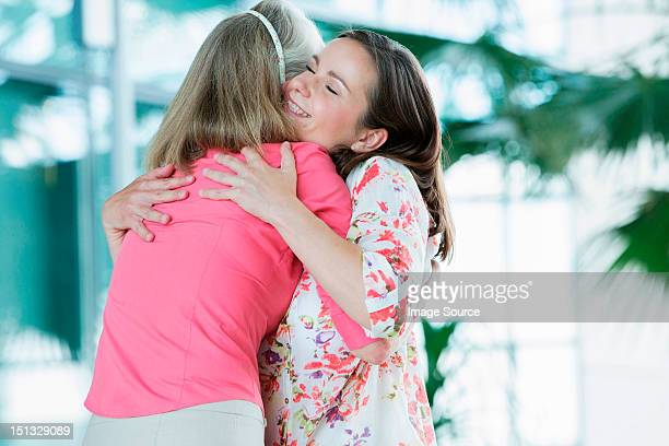 adult mother and daughter embracing - pink blouse stock pictures, royalty-free photos & images