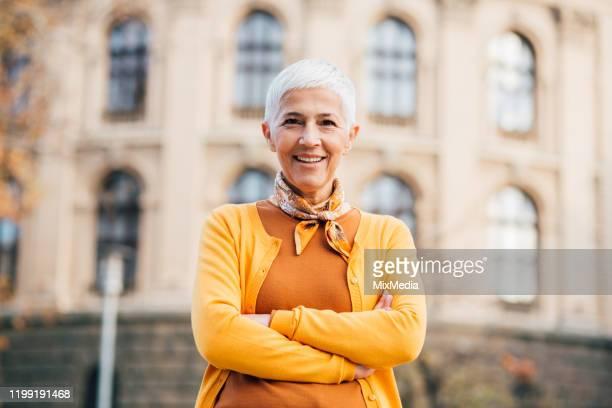 erwachsene person steht und lächelt zum fotografen - womens day stock-fotos und bilder