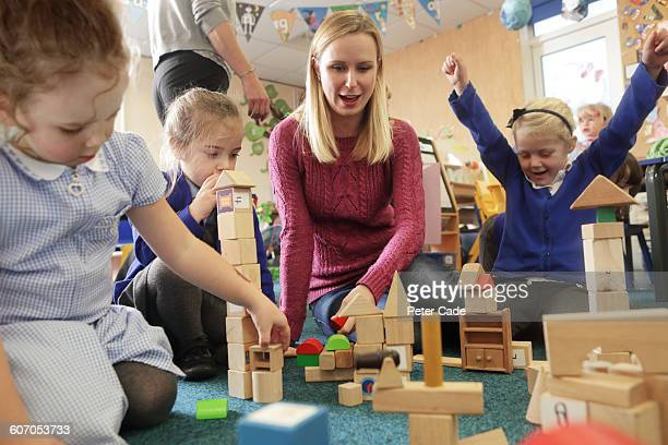 adult playing with children at school - instructor stock pictures, royalty-free photos & images
