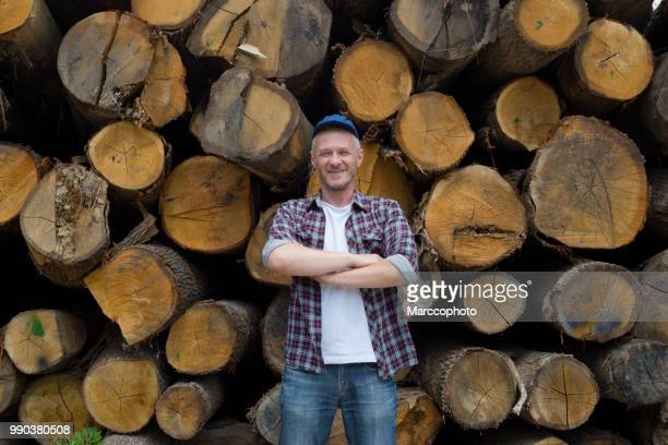 Adult satisfied lumberjack standing in front of large pile of timber