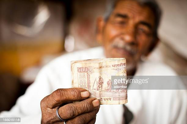 Adult Senior Indian Vendor Holding Rupees