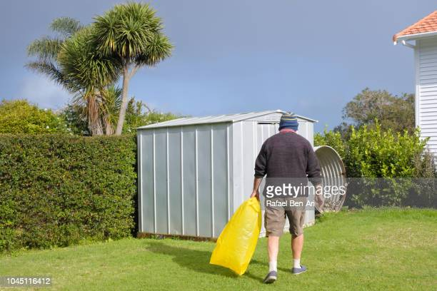 adult senior man carry a yellow plastic bag - rafael ben ari fotografías e imágenes de stock