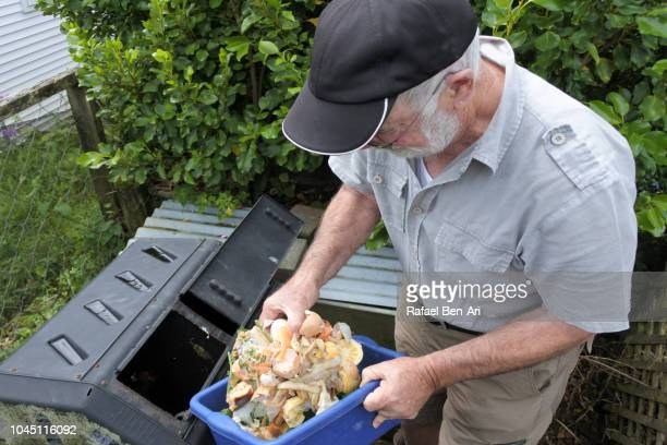 adult senior man composting food waste - rafael ben ari photos et images de collection