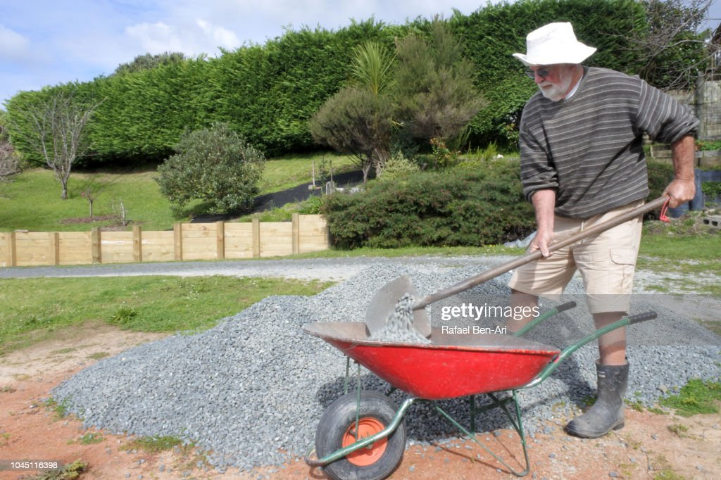 Adult Senior Man Filling a Wheel Barrel with Gravel : Stock Photo