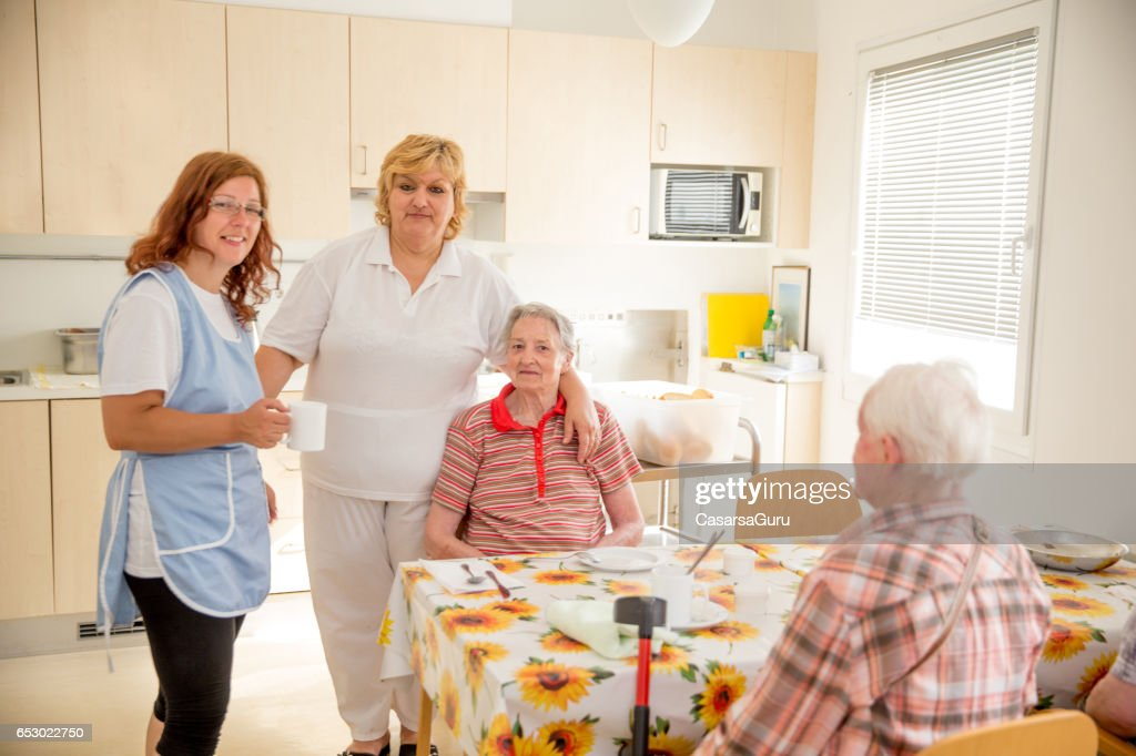Adult Senior socialiser dans la salle à manger du centre de soins : Photo