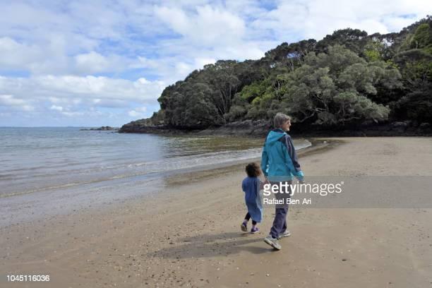 adult senior woman hiking outdoors with granddaughter - rafael ben ari fotografías e imágenes de stock