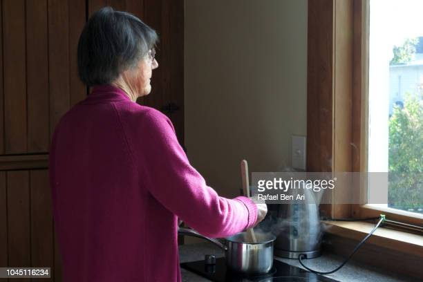 adult senior woman looking out of a window while cooking food - rafael ben ari photos et images de collection