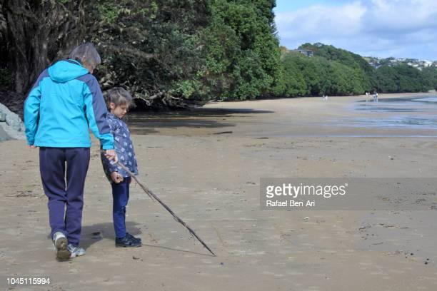 adult senior woman marking with wooden stick on sand with granddaughter - rafael ben ari fotografías e imágenes de stock
