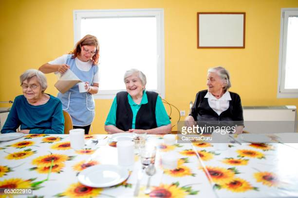adult seniors having breakfast at the care center - residential care stock photos and pictures