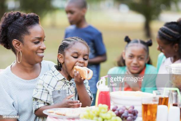 adult sisters and their children eating at cookout - aunt stock pictures, royalty-free photos & images