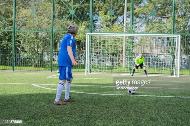 volwassen voetbalspeler rekent een penalty kick en maakt het doel om de doelman - verdediger voetballer stockfoto's en -beelden