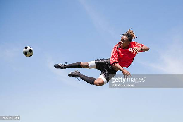 adulto giocatore di calcio calciare la palla in mid-air durante il gioco - tirare in rete foto e immagini stock