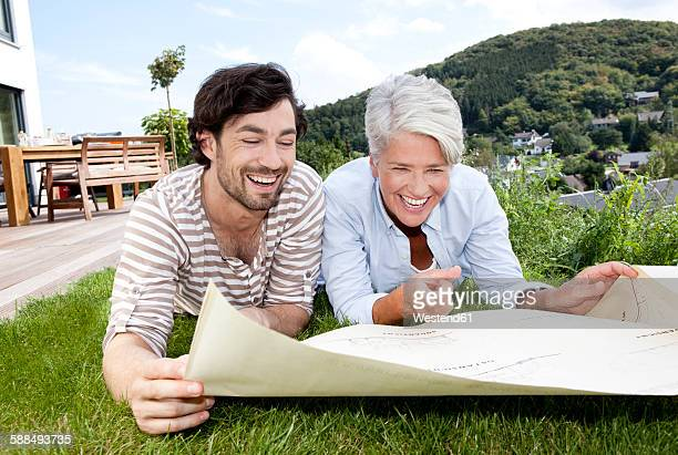 Adult son and mother lying on lawn looking at construction plan