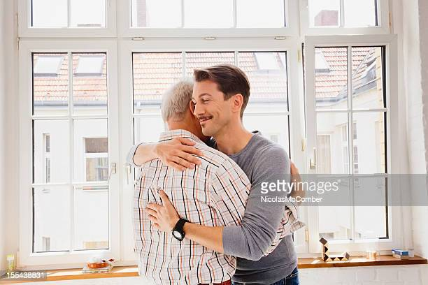 adult son hugging his dad - forgiveness stock pictures, royalty-free photos & images