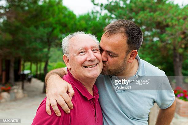 Adult son kissing and hugging his old father