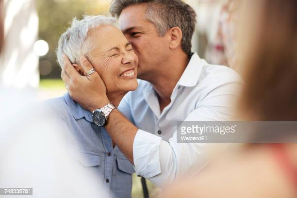 adult son kissing happy senior woman outdoors - mother and son stock photos and pictures