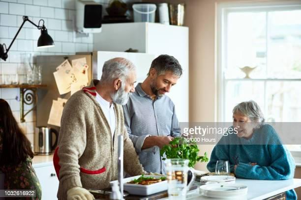 adult son preparing meal for parents in kitchen with mother watching and smiling - nur erwachsene stock-fotos und bilder