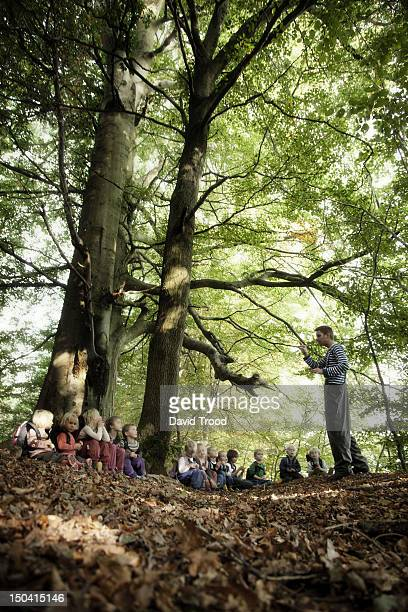 Adult storytelling to children in the forest