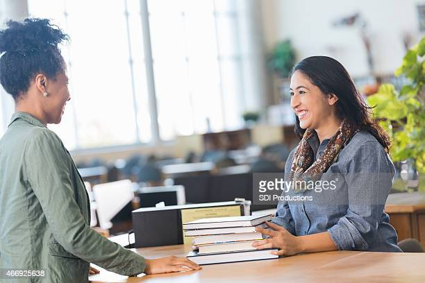 Adult student checking out books in local college library