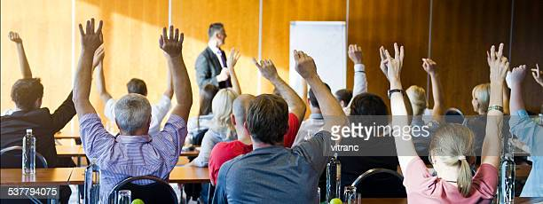 Adult students raising hands on seminar