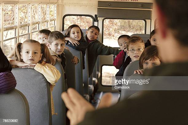 adult talking to children on school bus - field trip stock pictures, royalty-free photos & images