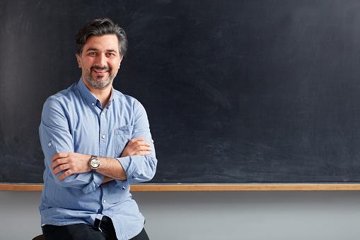 Adult teacher posing on blackboard. 1089058072