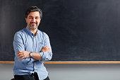 Adult teacher posing on blackboard.