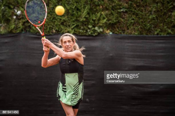 Adult Tennis Player Swinging her Racket and Looking at the Ball Mid Air