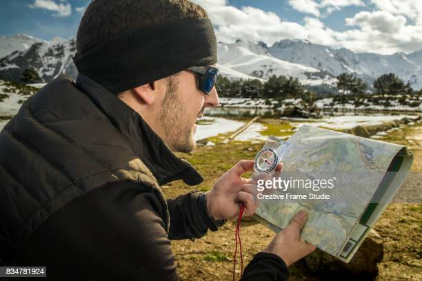 adult trail runner checks a map using a compass. - cartography stock photos and pictures