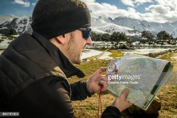 Adult trail runner checks a map using a compass.