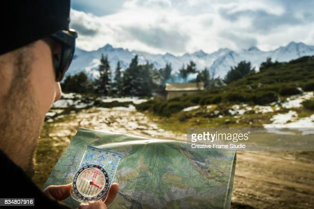 Adult trail runner checks a map with a compass.