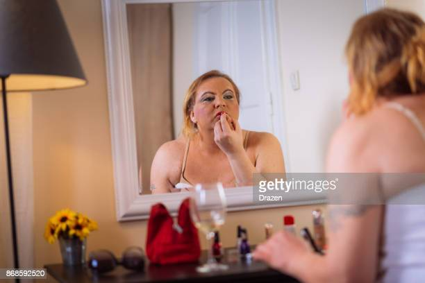 adult transgender person putting lipstick in front of the mirror - intersex stock photos and pictures