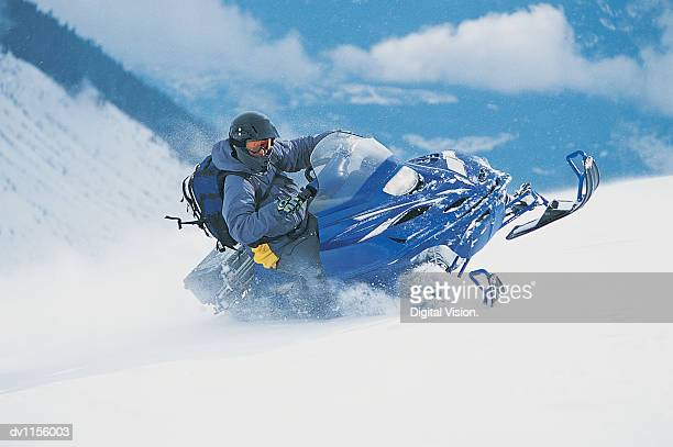 adult turning a snow mobile at speed in the snow - snowmobiling - fotografias e filmes do acervo