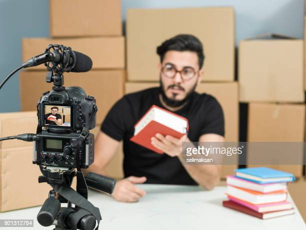 Adult Vlogger Man Recording Video Of Book Review For Video Blogging