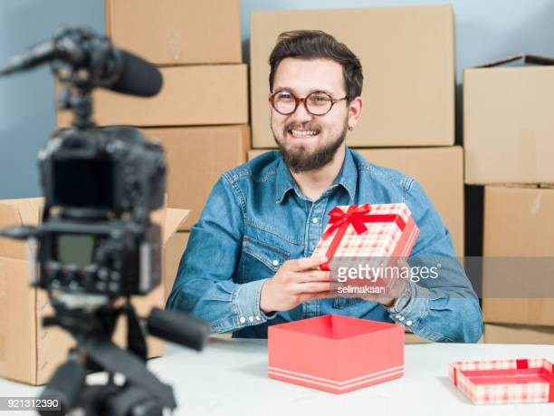 Adult Vlogger Man Recording Video Of Unboxing Items For Video Blogging