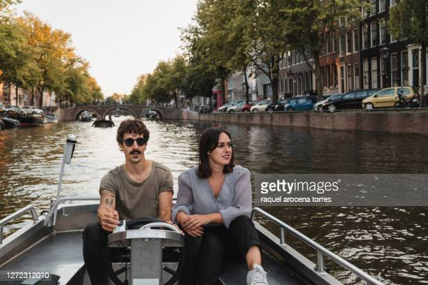 adult white couple in a boat on the canals of amsterdam - netherlands stock pictures, royalty-free photos & images
