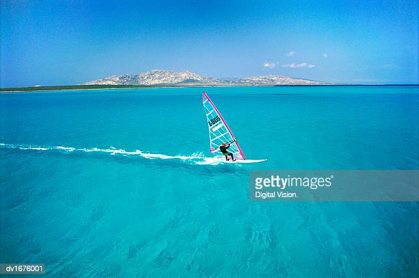 Adult Windsurfing in the Sea off the Coast of Sardinia, Italy