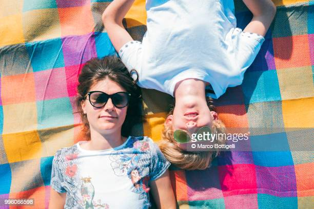 adult woman and her son relaxing on a colorful mat - colorful background stock photos and pictures