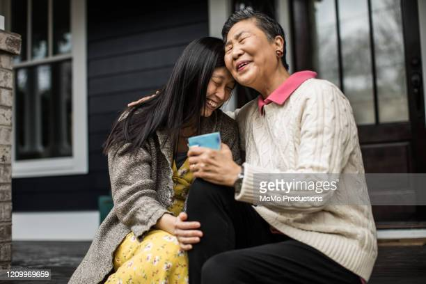 adult woman and senior mother talking on front porch - daughter stock pictures, royalty-free photos & images