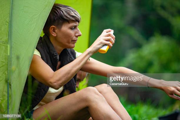 Adult Woman Applying Mosquito Repellent While Camping