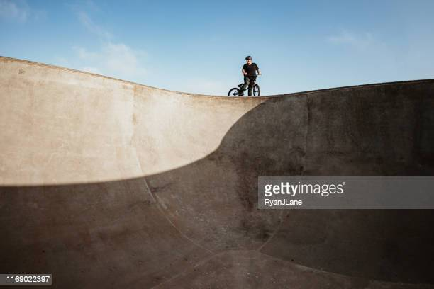 adult woman bmx bike rider at ramp park - half pipe stock pictures, royalty-free photos & images