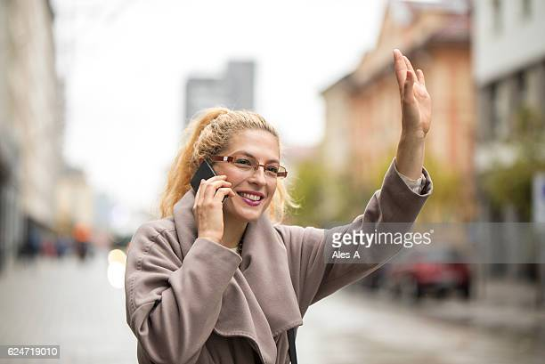 Adult woman catching a taxi