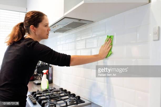 adult woman cleaning home kitchen - rafael ben ari stock-fotos und bilder