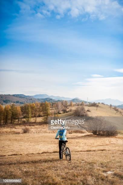 mujer adulta cycler fondo mirando a ver - cross country cycling fotografías e imágenes de stock