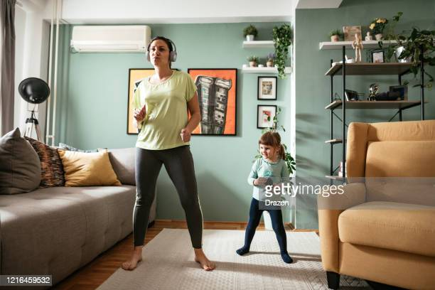 adult woman dancing at home during quarantine with three year old daughter - wellbeing stock pictures, royalty-free photos & images
