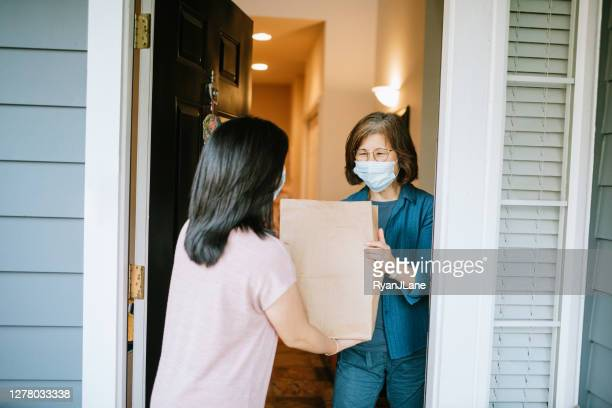 adult woman delivers groceries to her mother - giving tuesday stock pictures, royalty-free photos & images