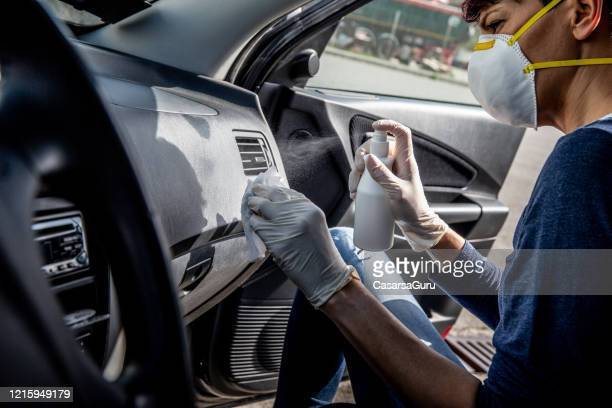 adult woman disinfecting car dash board with antiseptic and wet wipe - stock photo - disinfection stock pictures, royalty-free photos & images