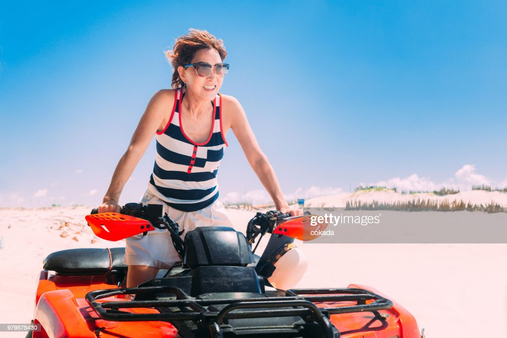 Adult woman driving off road ATV : Stock Photo