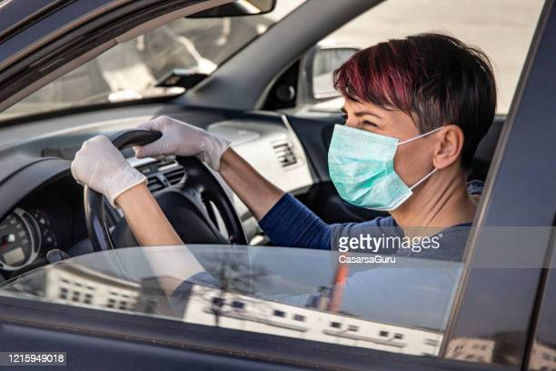 adult woman driving to work wearing n95 face mask and surgical gloves during covid-19 outbreak - stock photo - driving mask stock pictures, royalty-free photos & images