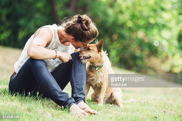 adult woman enjoying time with pet dog - animal themes stock pictures, royalty-free photos & images